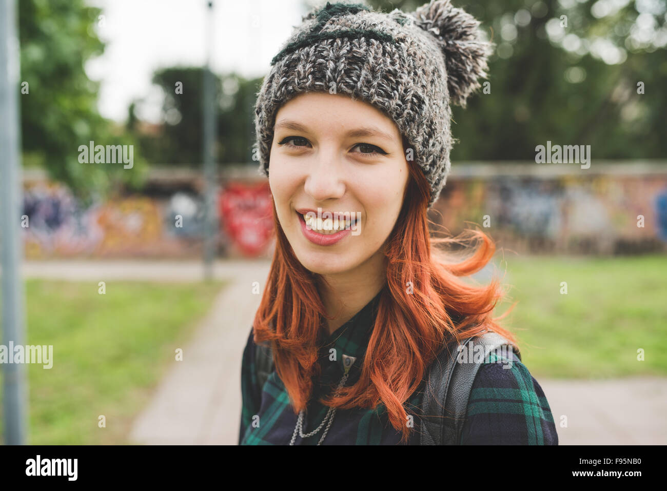 Portrait of young handsome caucasian redhead straight hair woman wearing hat looking in camera smiling - carefree, - Stock Image
