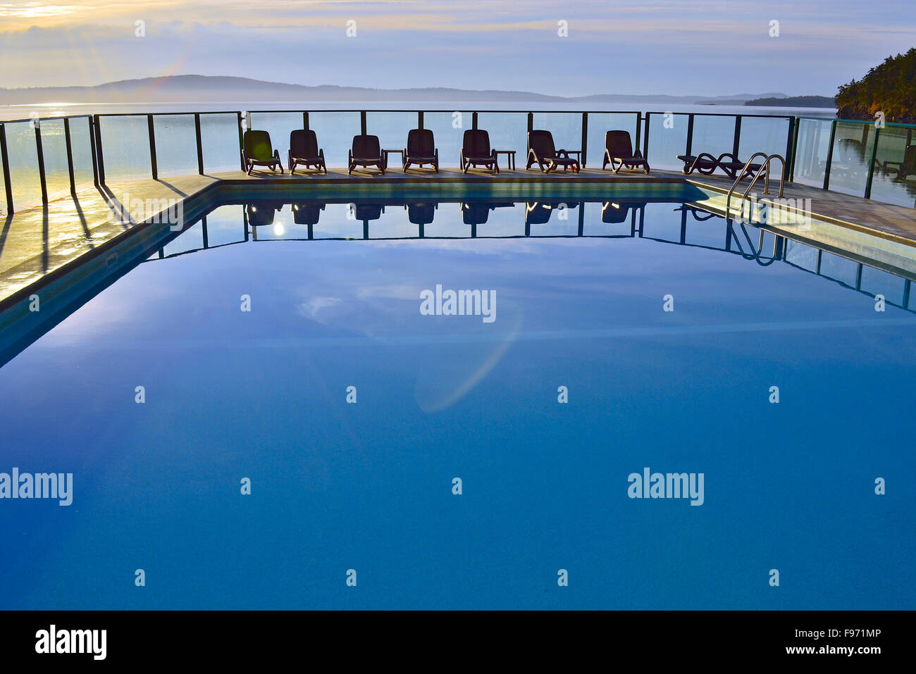 A horizontal image of an outdoor swimming pool with a line of chairs at a vacation resort on Vancouver Island B.C. - Stock Image