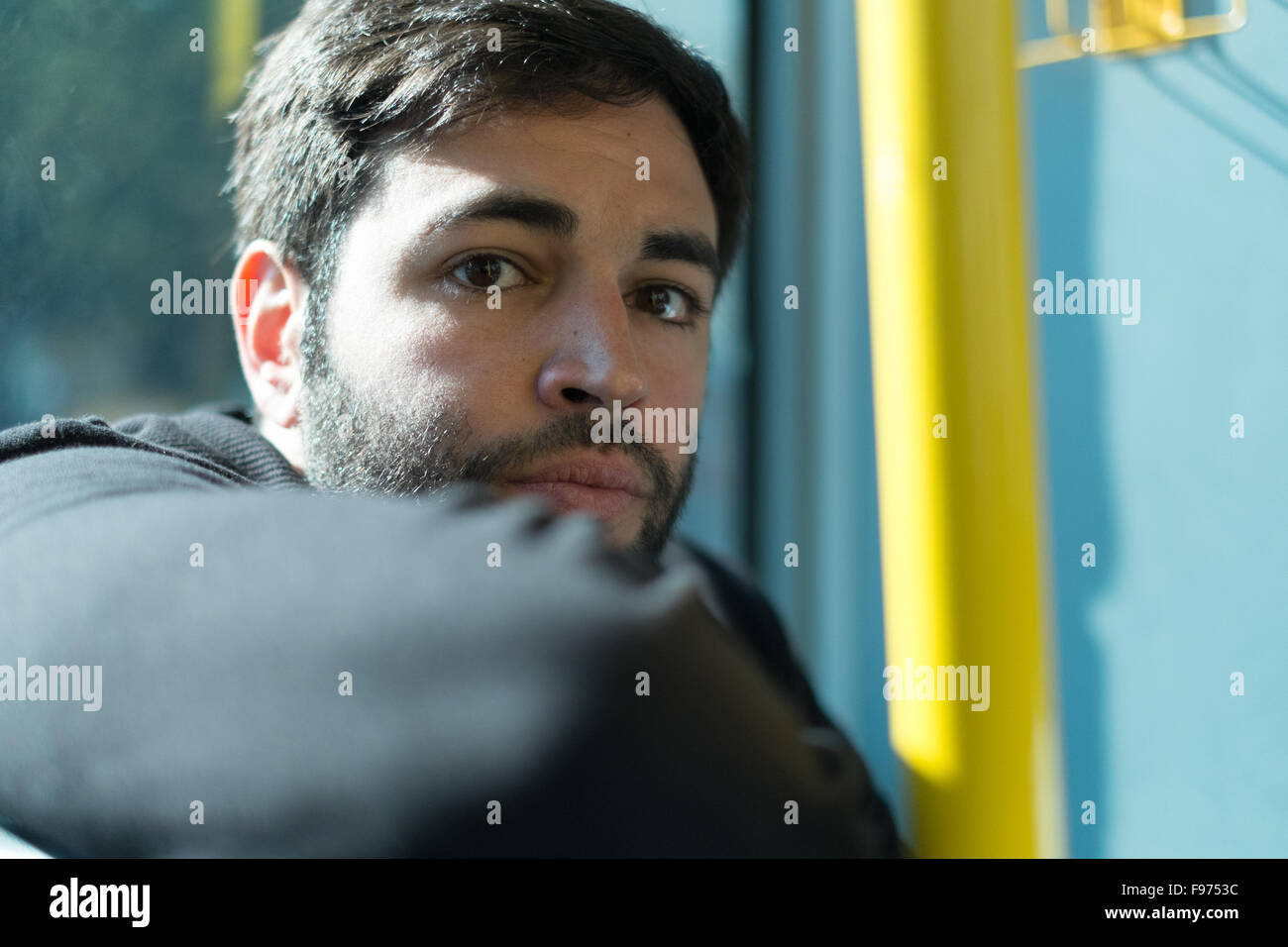 Portrait Of Young Man Traveling In Train - Stock Image