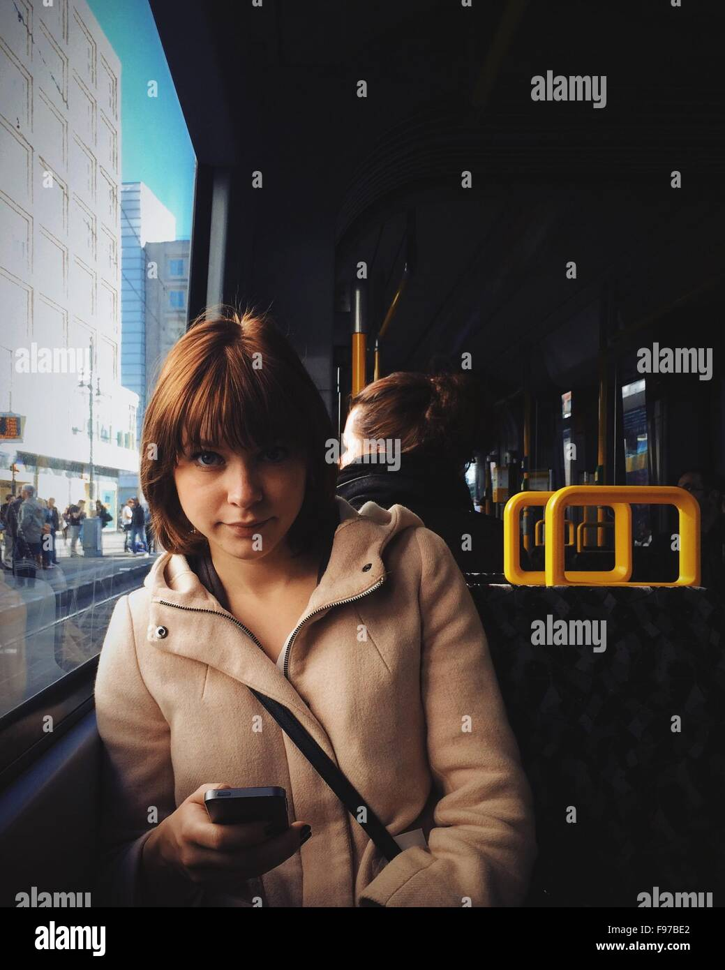 Portrait Of Young Woman Using Mobile Phone While Traveling In Tram - Stock Image