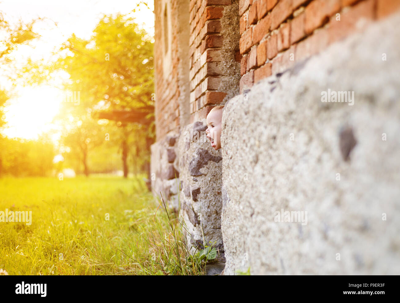 Cute little boy playing and having fun outside in a garden in front of an old house - Stock Image