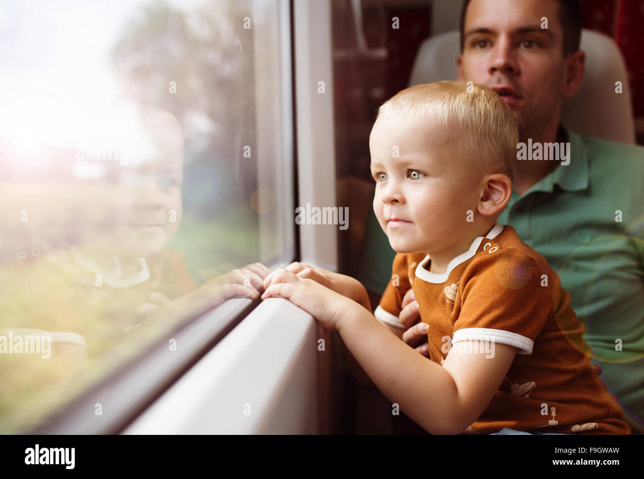 Father with son in his lap traveling in train. - Stock Image