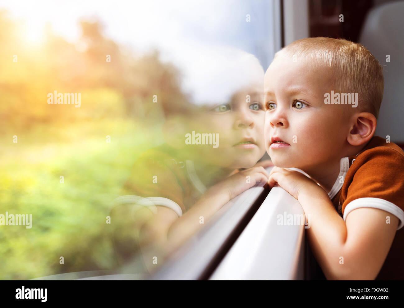 Little boy traveling in train looking outside the window. - Stock Image