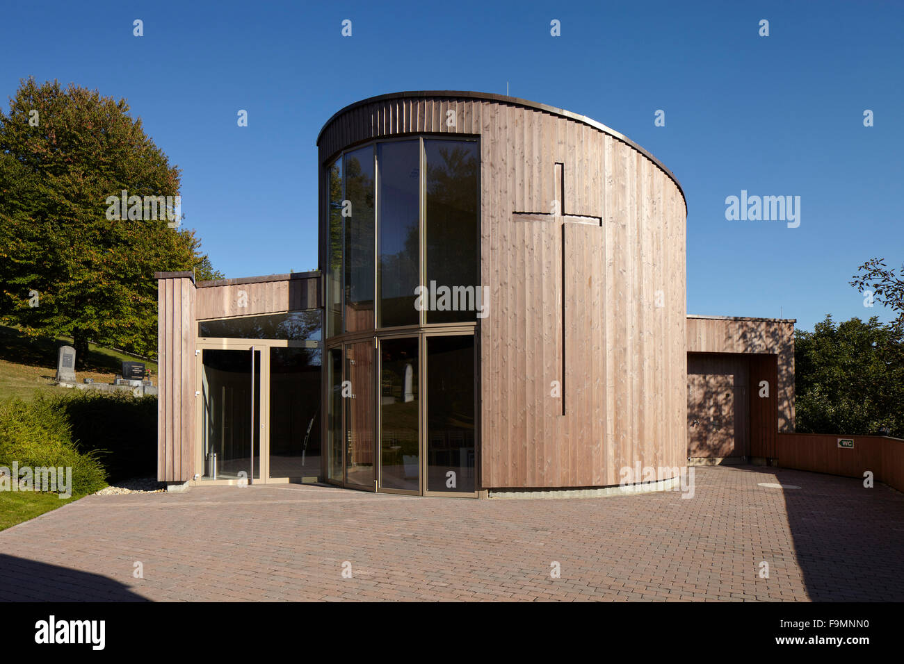 Exterior of a modern cemetery chapel with full height glazed windows at Oberwart, Austria - Stock Image