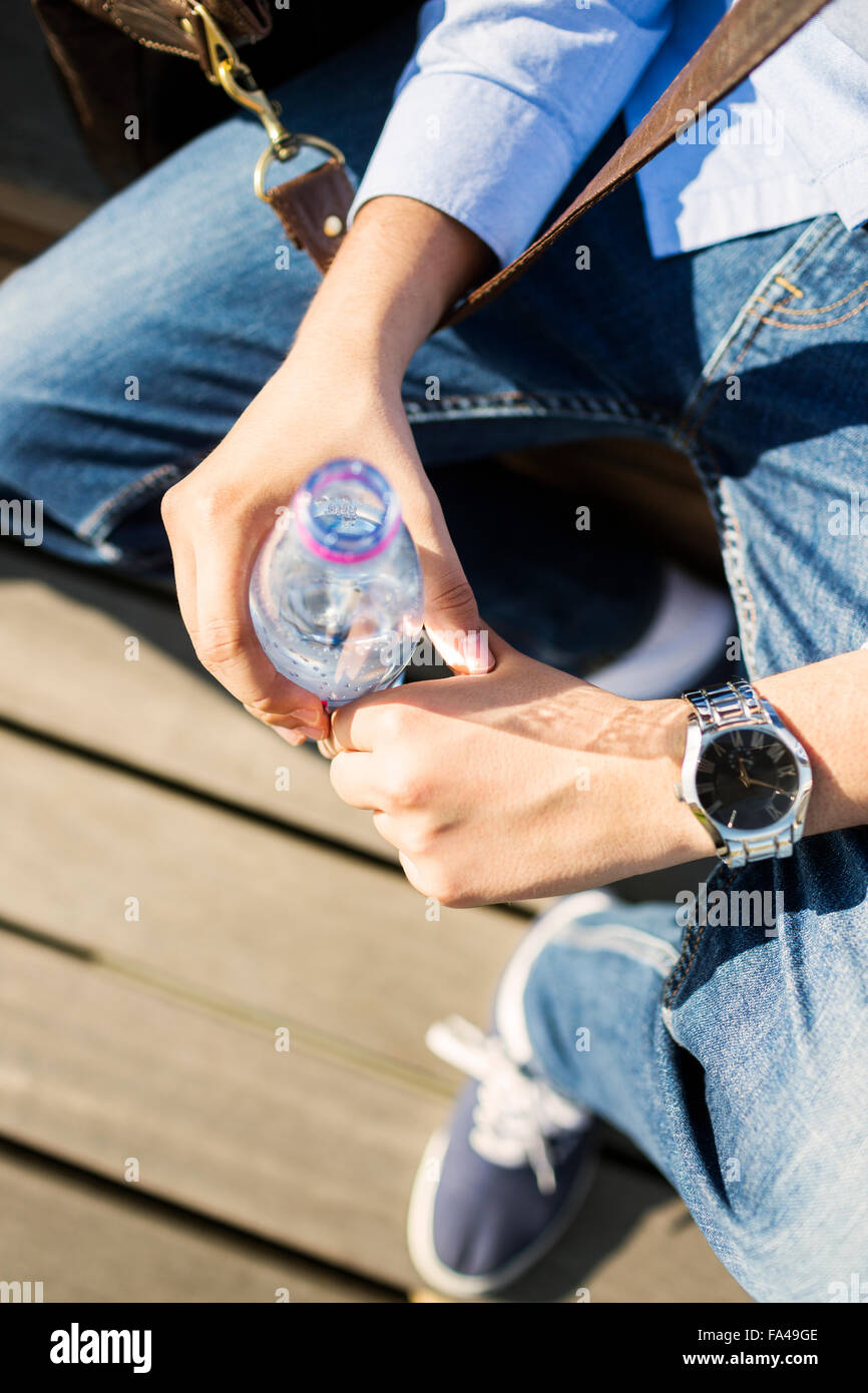 High angle view of young man holding water bottle outdoors - Stock Image