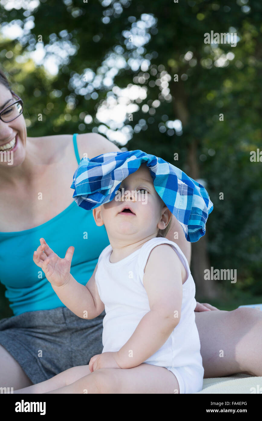 Baby boy playing with trousers on his head, Munich, Bavaria, Germany - Stock Image