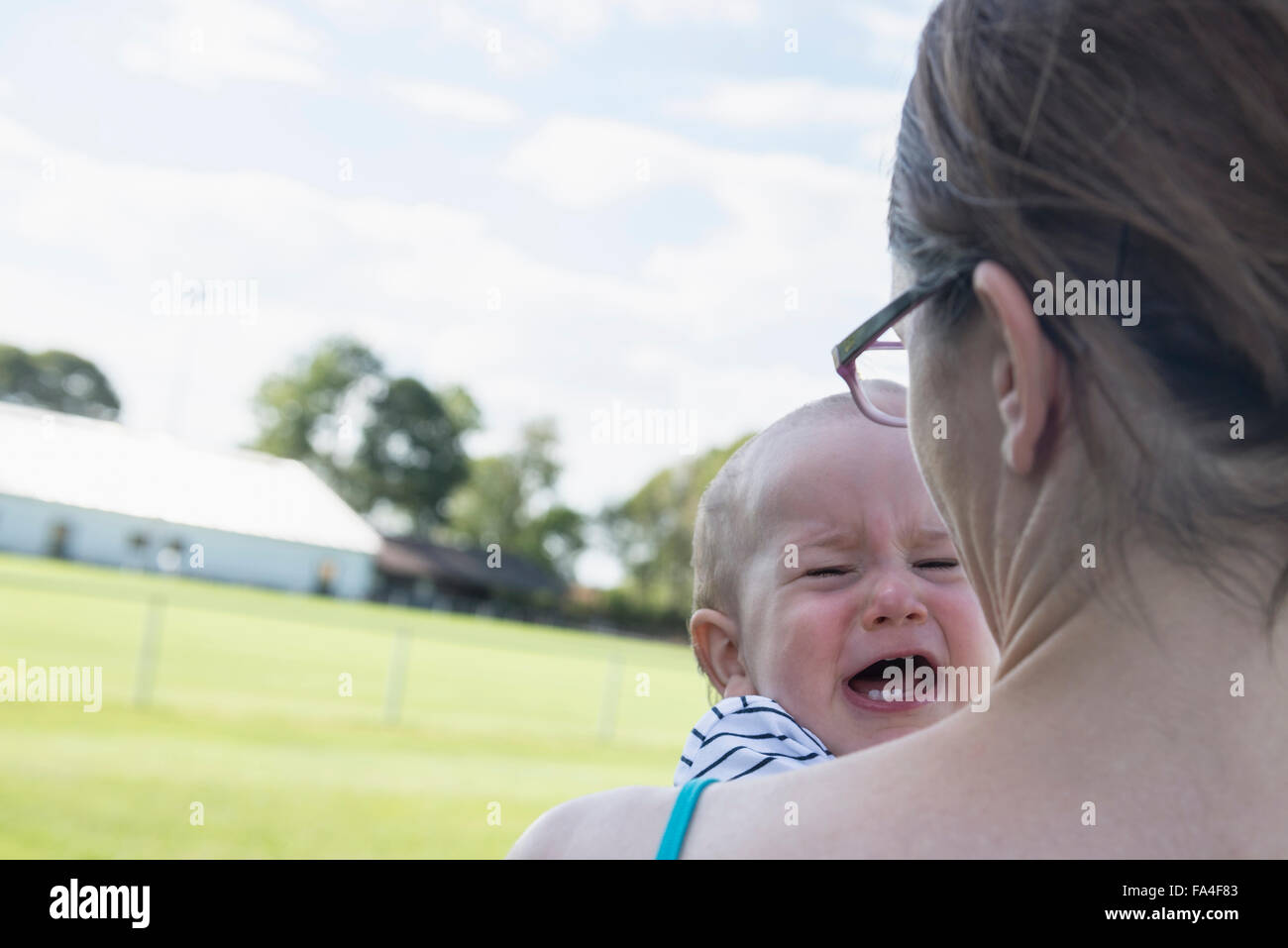 Baby boy crying in the arms of his mother, Munich, Bavaria, Germany - Stock Image