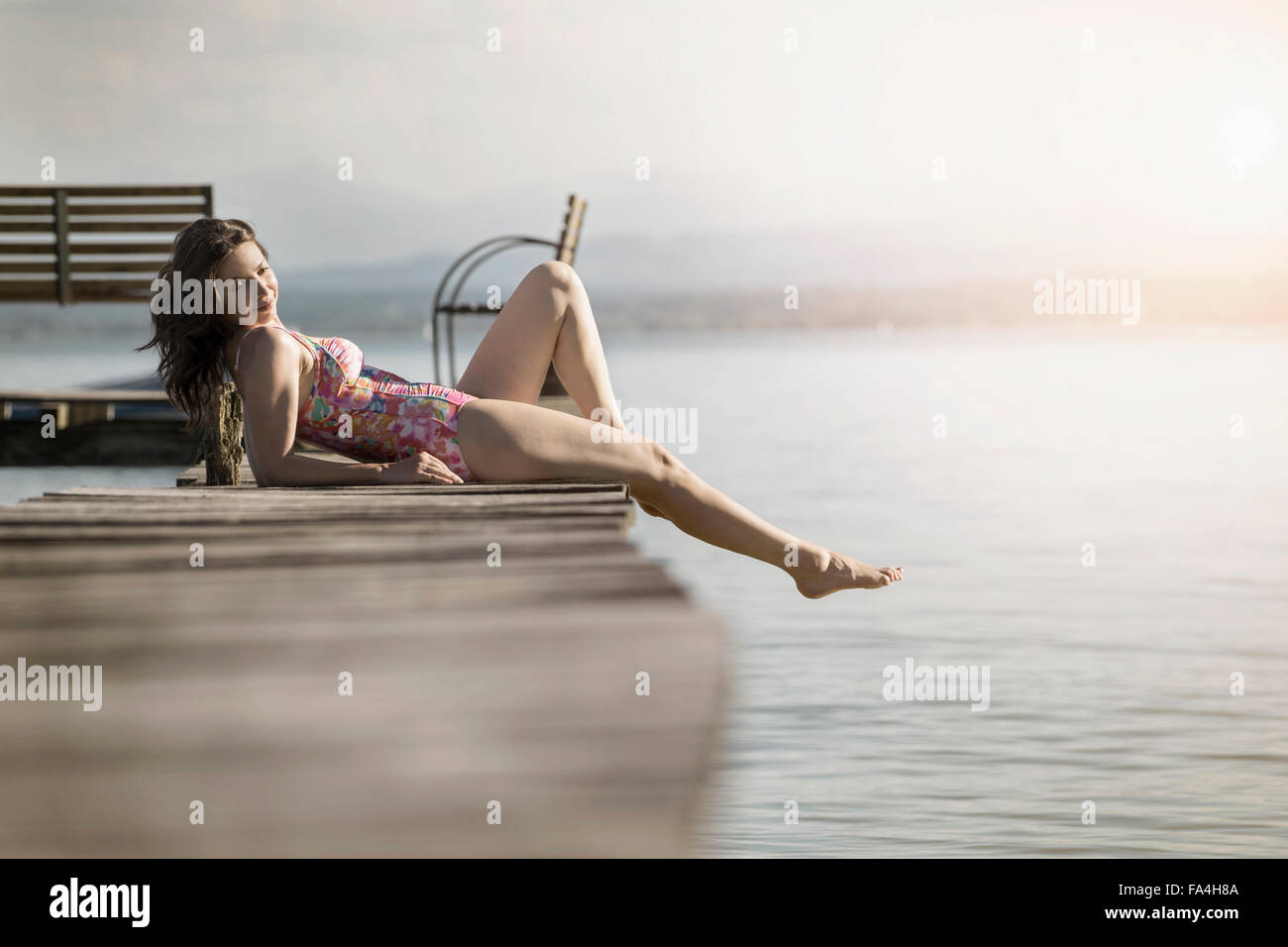 Mature woman lying in swimsuit on pier, Bavaria, Germany - Stock Image