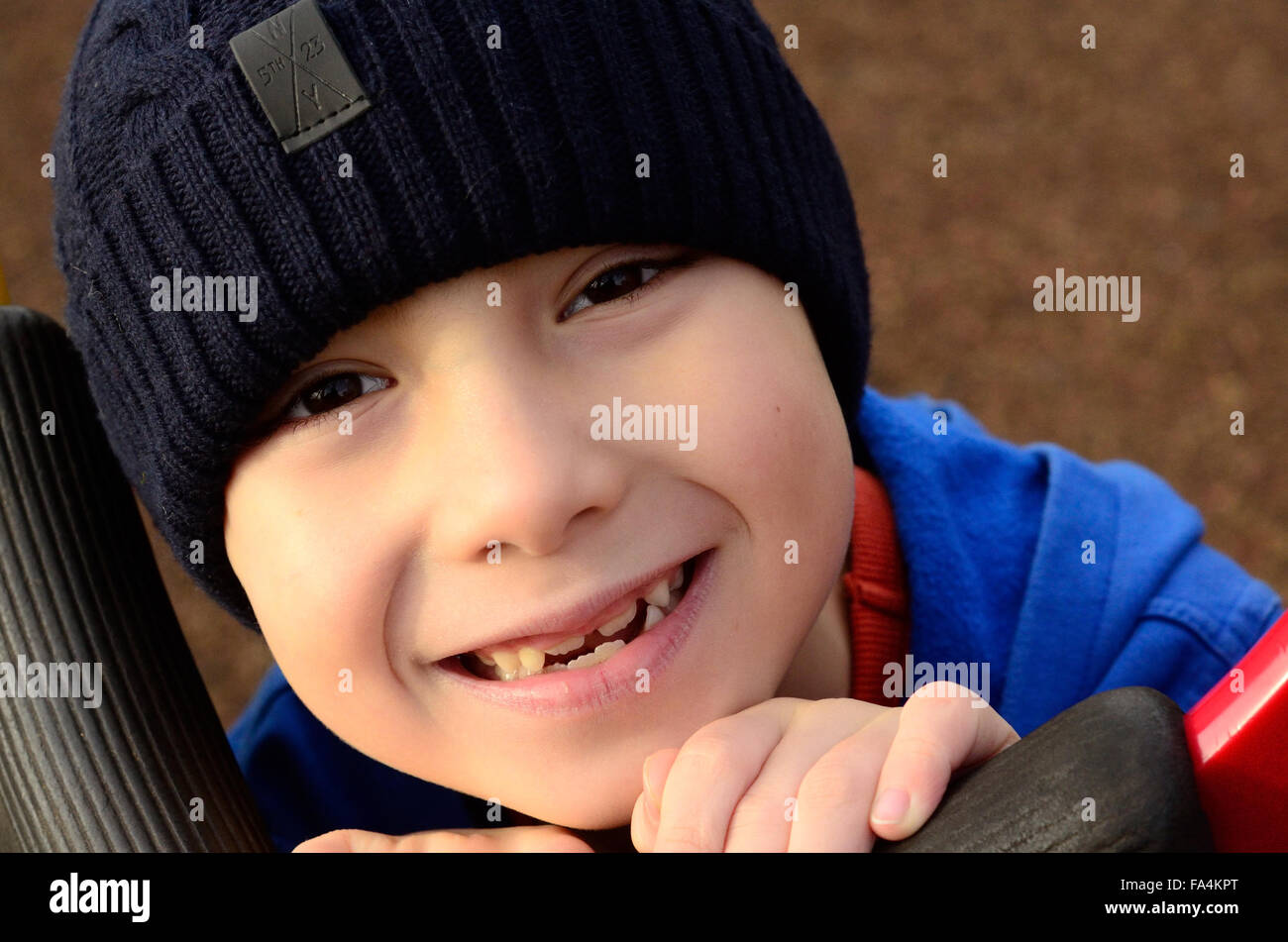 a-young-boy-with-a-gappy-smile-wearing-a-beanie-hat-FA4KPT.jpg
