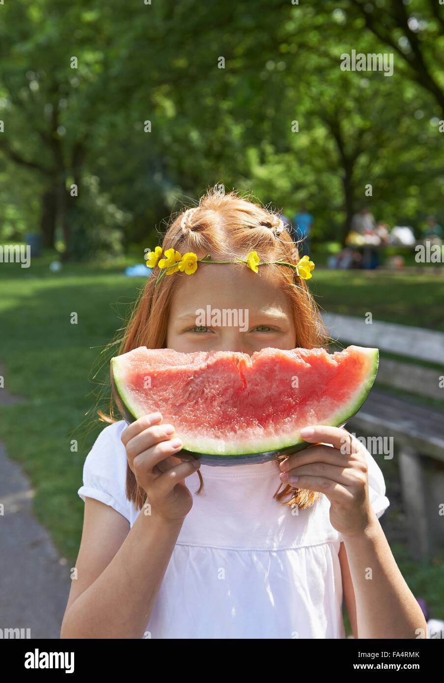 Portrait of a girl enjoying slice of watermelon at picnic, Munich, Bavaria, Germany - Stock Image
