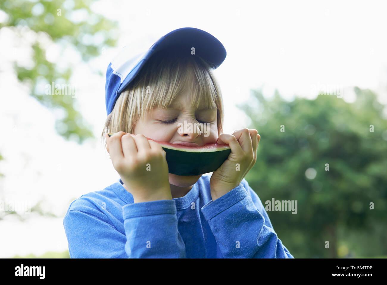 Boy enjoying slice of watermelon at picnic, Munich, Bavaria, Germany - Stock Image