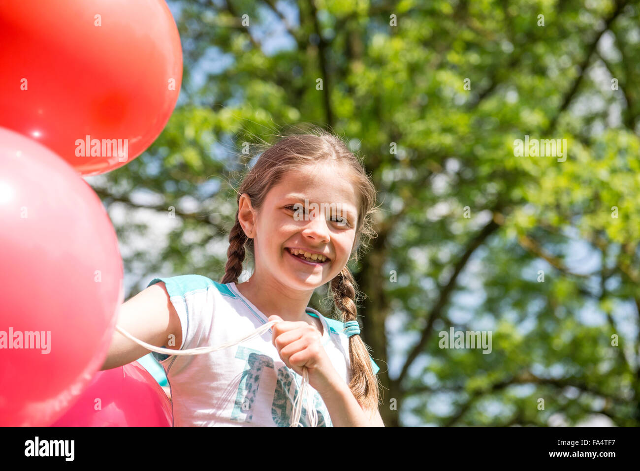 Portrait of a smiling girl holding red balloons, Munich, Bavaria, Germany - Stock Image