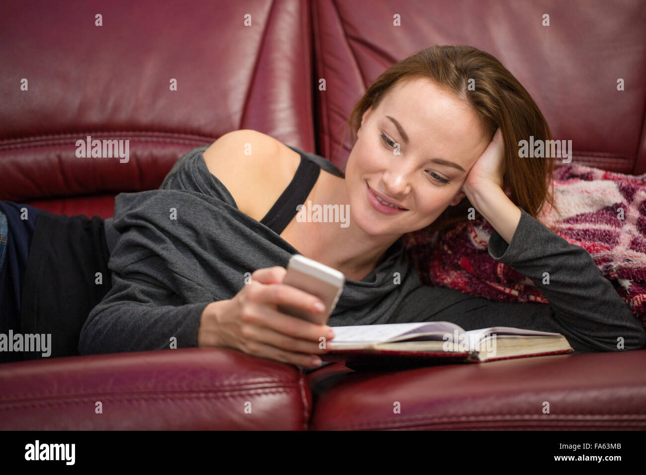 Smiling pretty young redhead woman reading book and using mobile phone at home - Stock Image