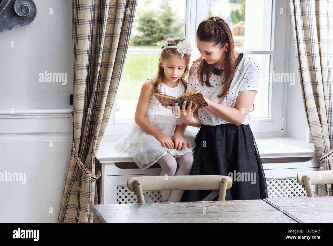 Caring mother teaching cute daughter how to read - Stock Image
