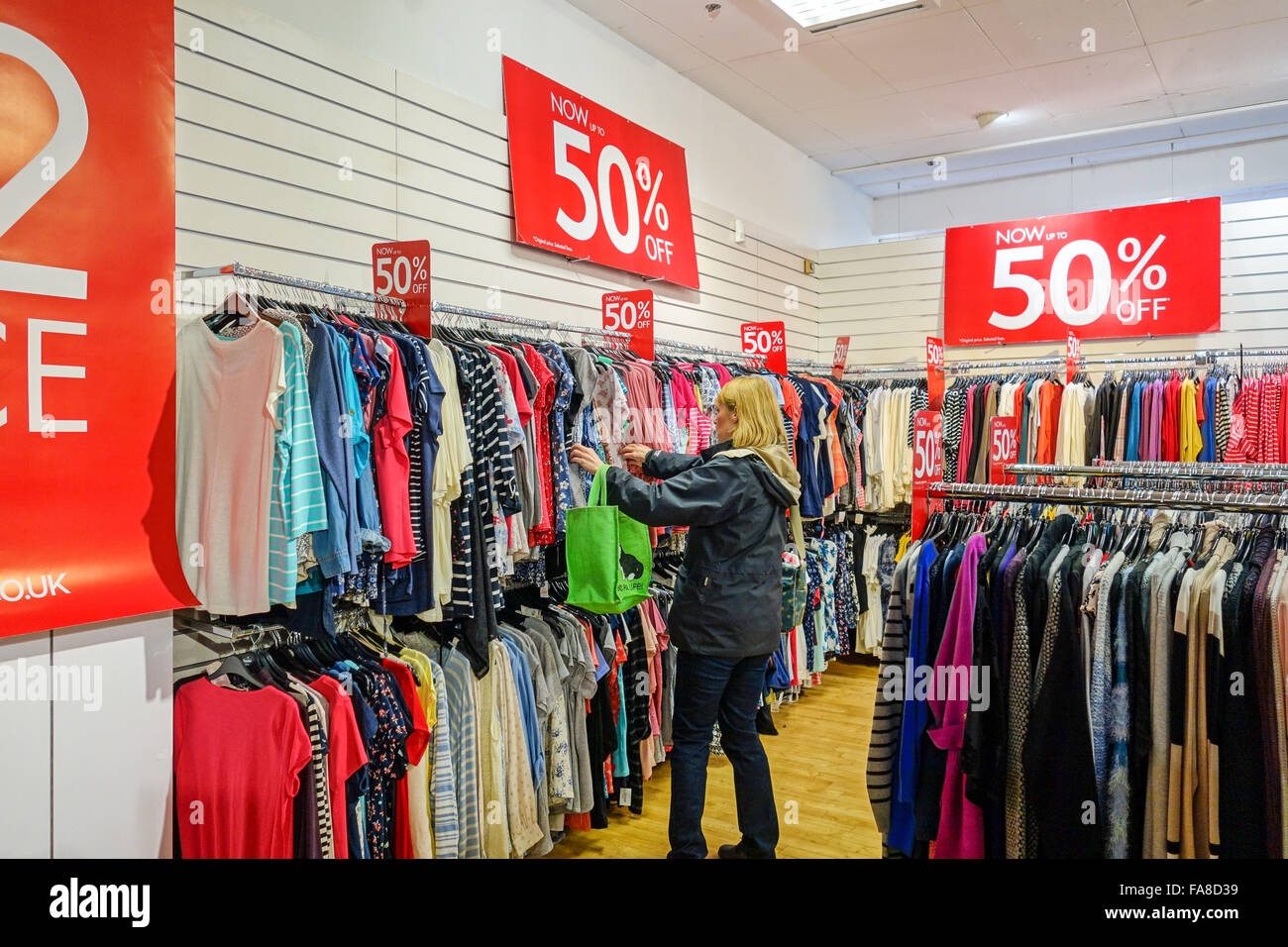 A woman looking at clothes in a sale hanging on rails in a shop with 50% off the prices Stock Photo