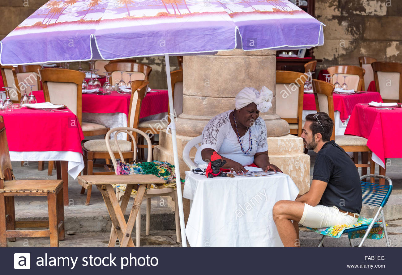 Afro Caribbean Fortune Teller in Old Havana,Cuba. The lady belongs to a variation of African religions that are - Stock Image