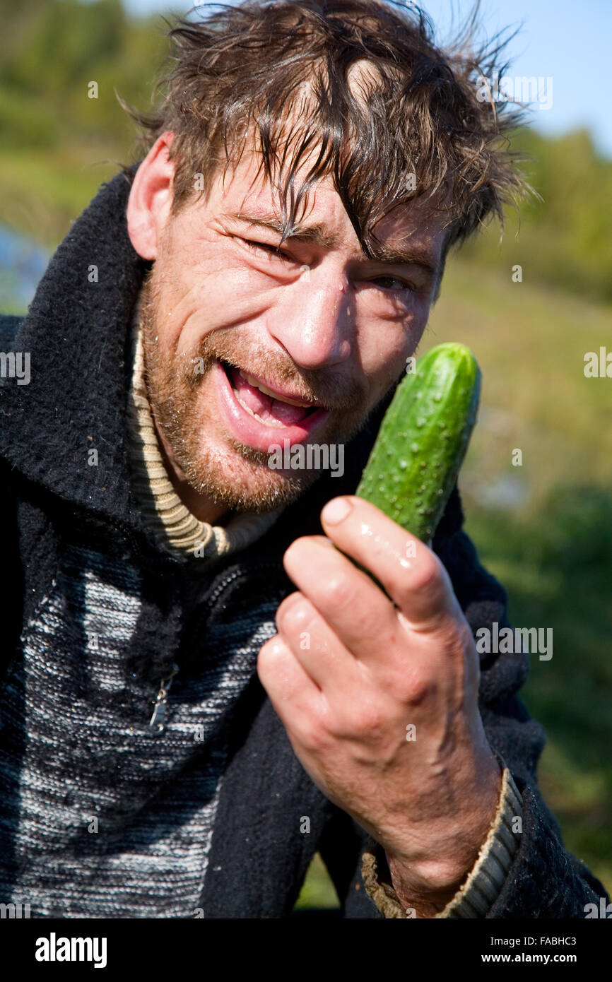tramp eats green cucumber Stock Photo