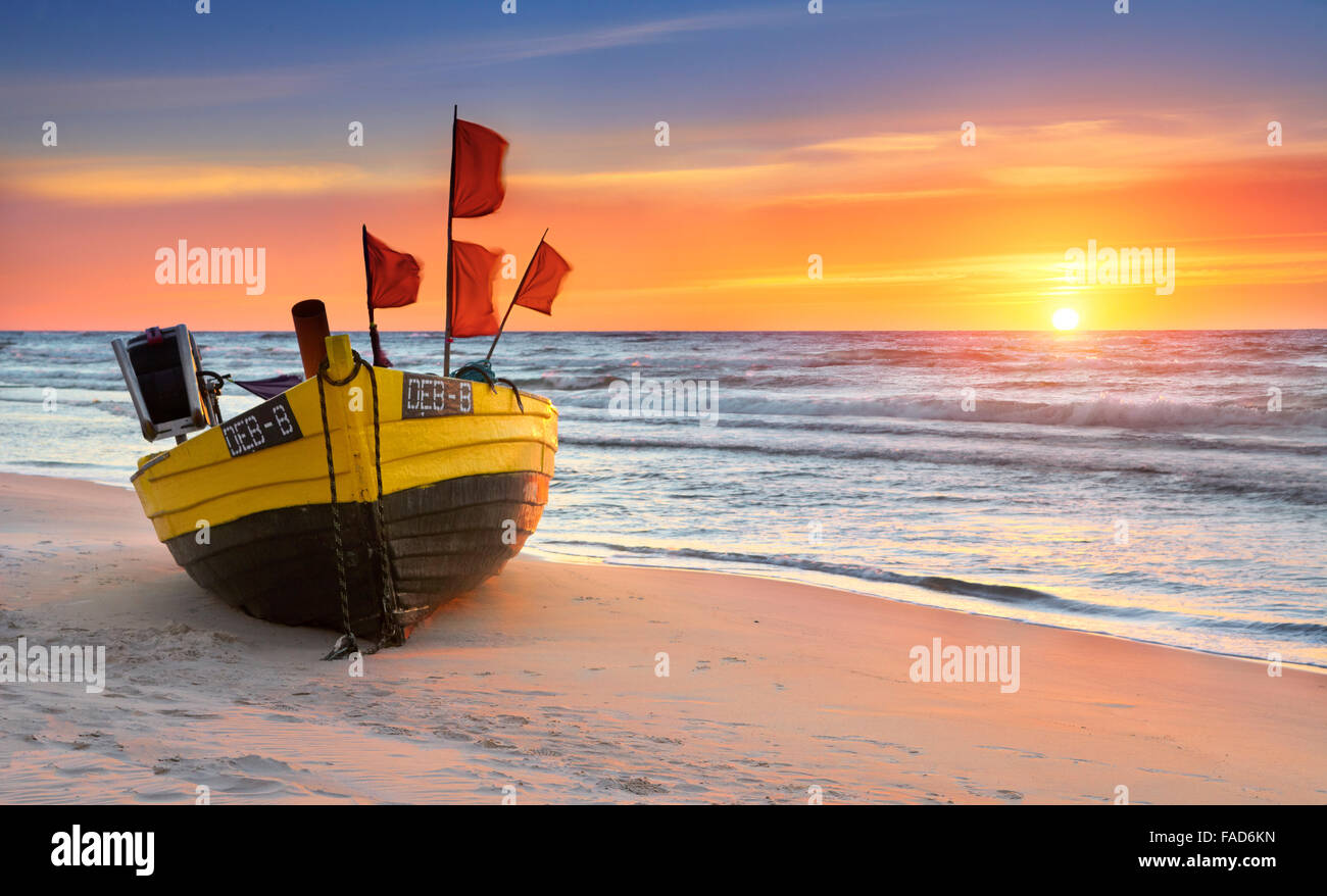 Fishing boat at the beach, sunset time at Baltic Sea, Pomerania, Poland - Stock Image