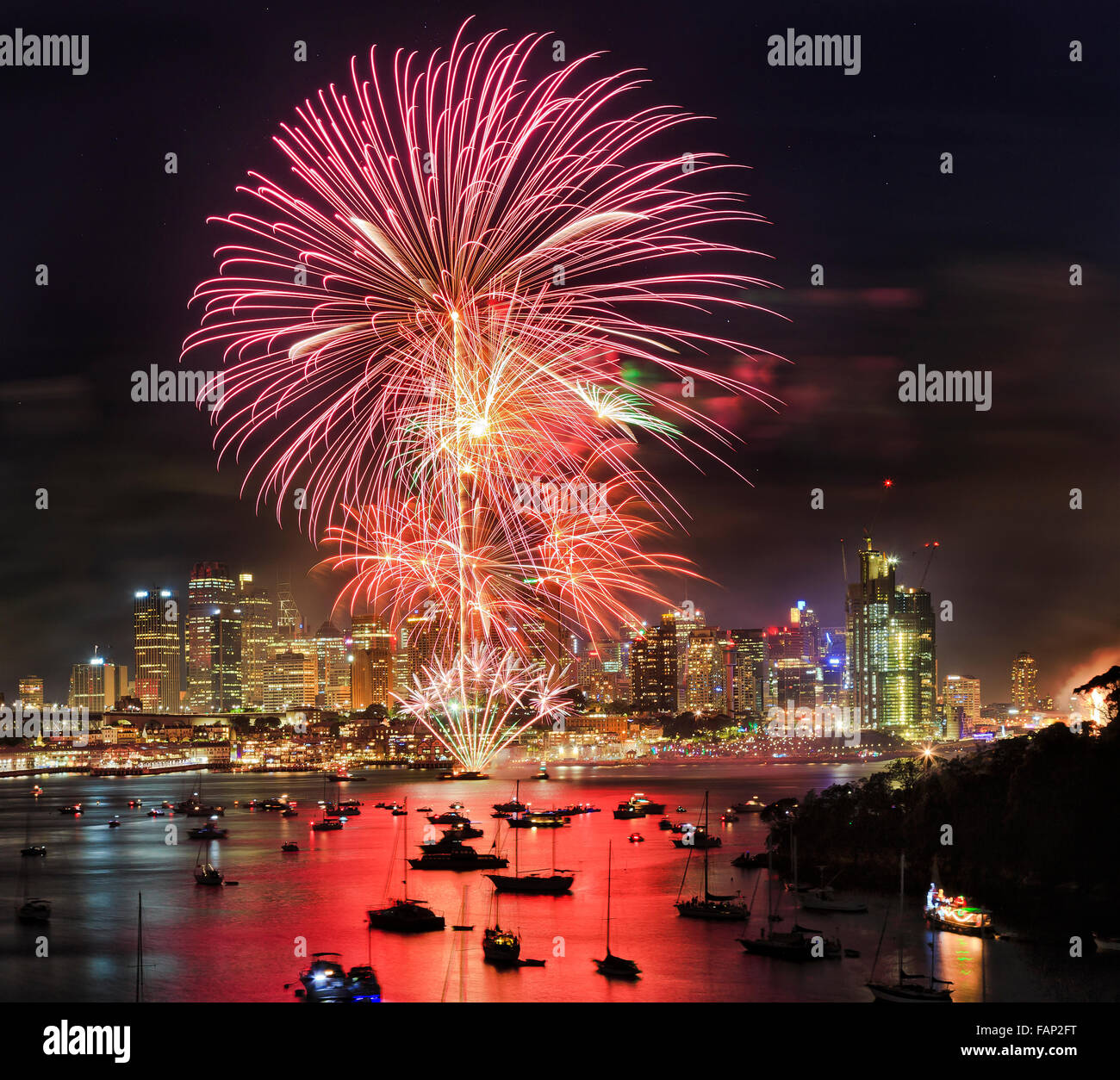 New year fireworks in Sydney from elevated lookout at Berrys bay over Sydney harbour with CBD skyscrapers under - Stock Image