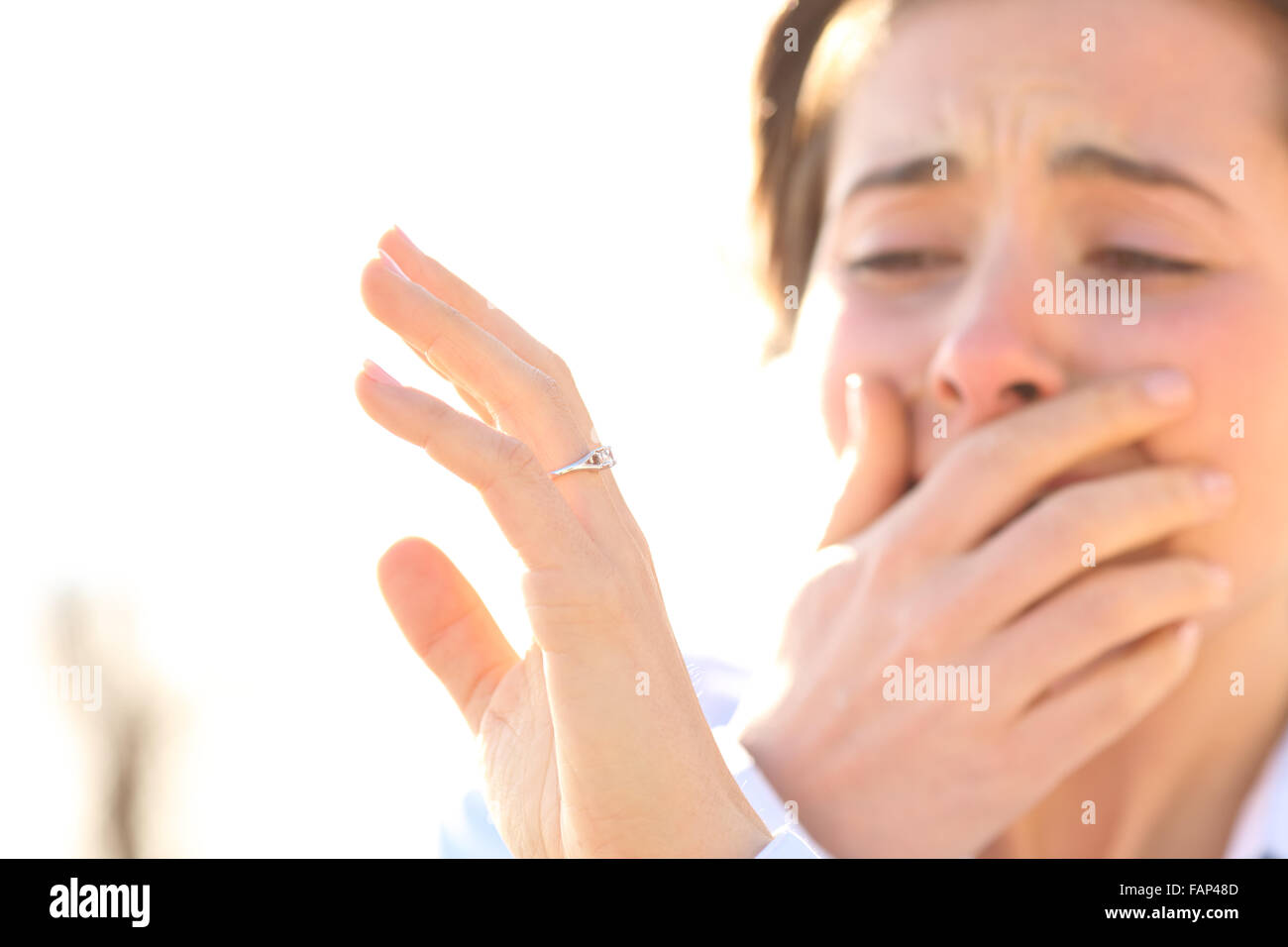 Woman crying while watching an engagement ring after proposal in a sunny day - Stock Image