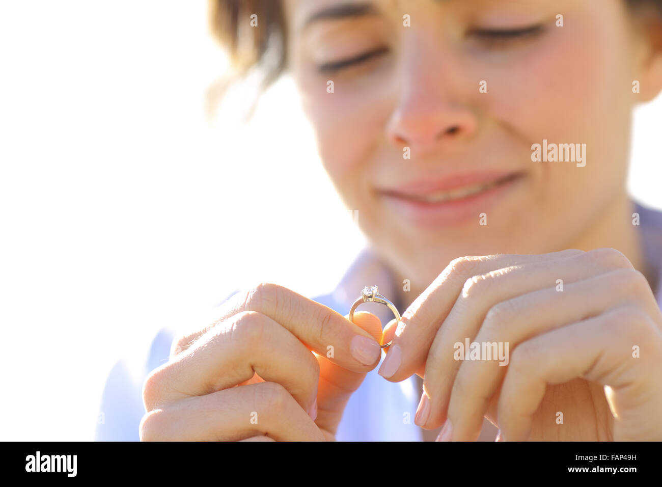 Sad girlfriend crying while is looking her engagement ring - Stock Image