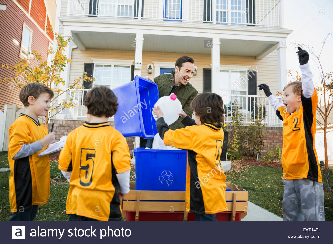 Coach and boys sports team gathering recycling neighborhood - Stock Image