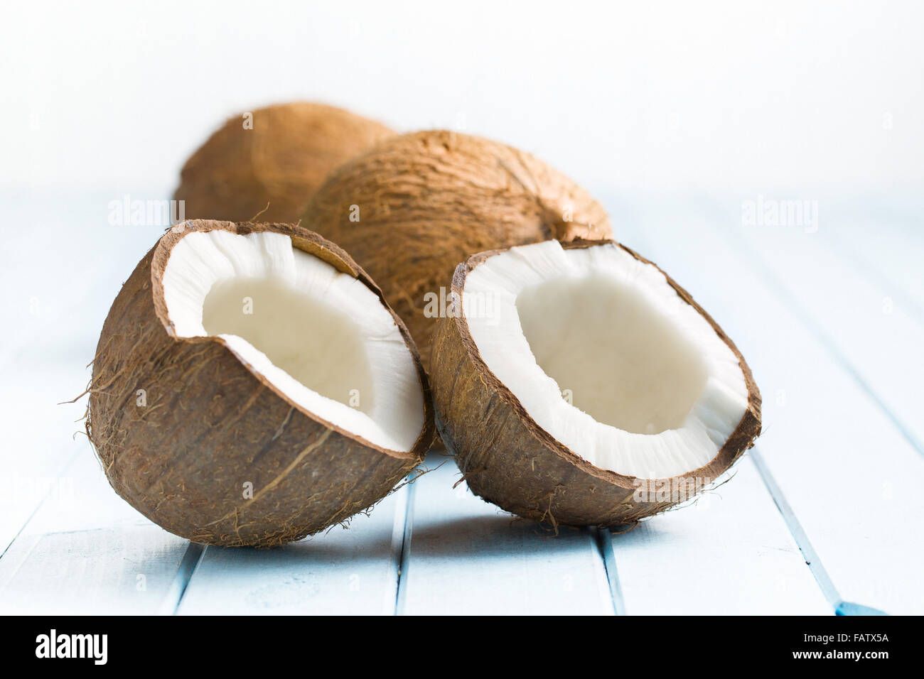 halved coconut on kitchen table - Stock Image