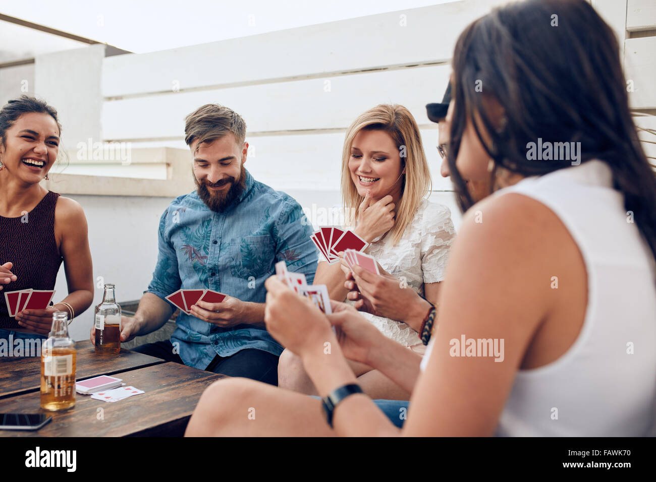 Group of friends sitting at a wooden table and playing cards. Young people playing a game of cards during a party. - Stock Image