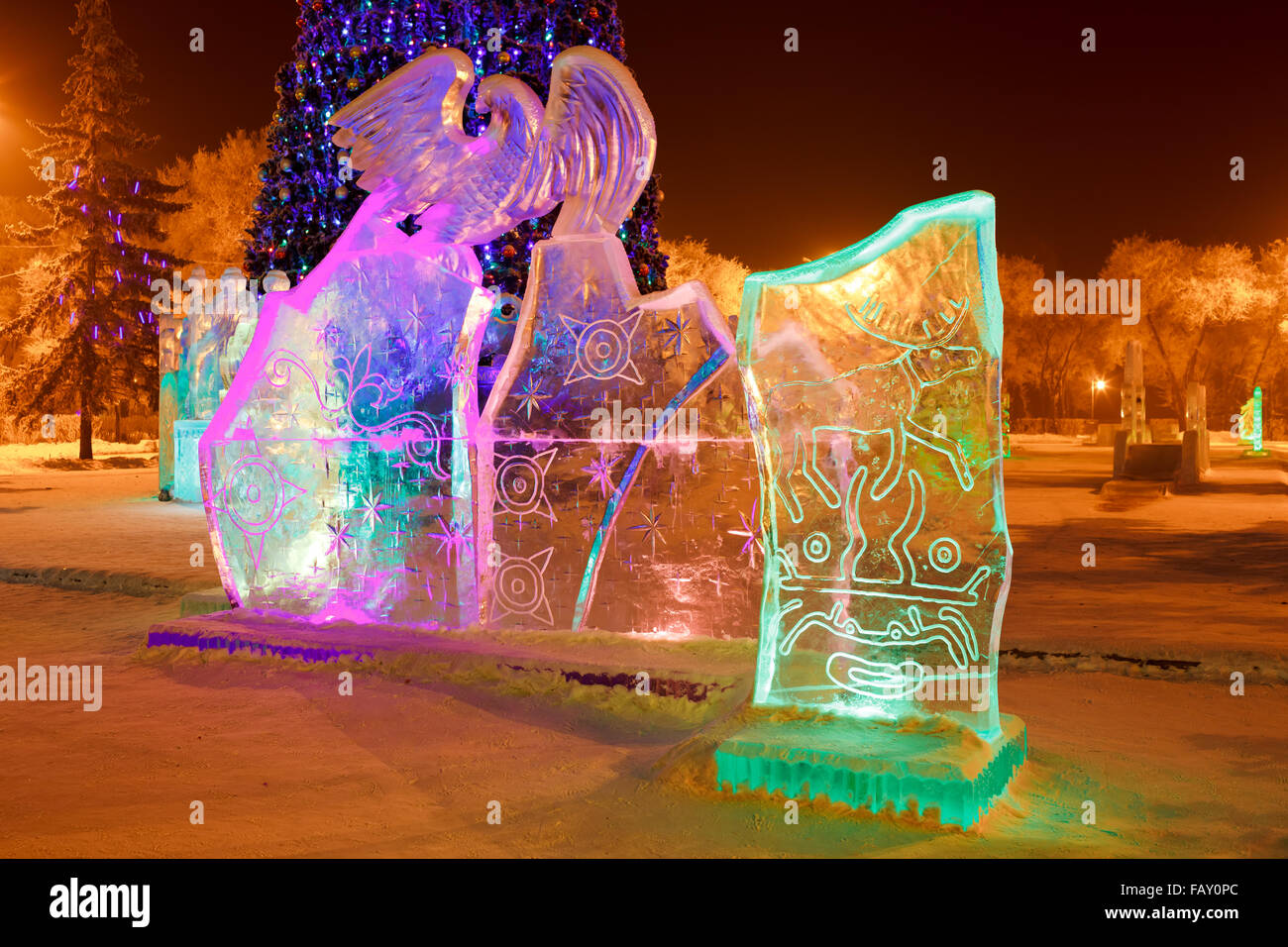 Ice sculpture in the city park on Christmas and New Year with cave paintings of deer, mythical creatures, solar - Stock Image
