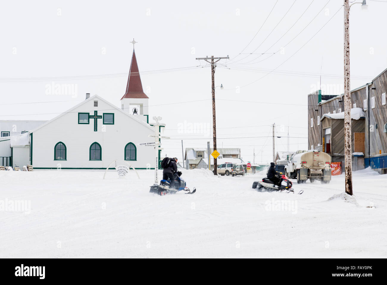 Two male native Alaskans ride snowmobiles in downtown Barrow, North Slope, Arctic Alaska, USA, Winter Stock Photo