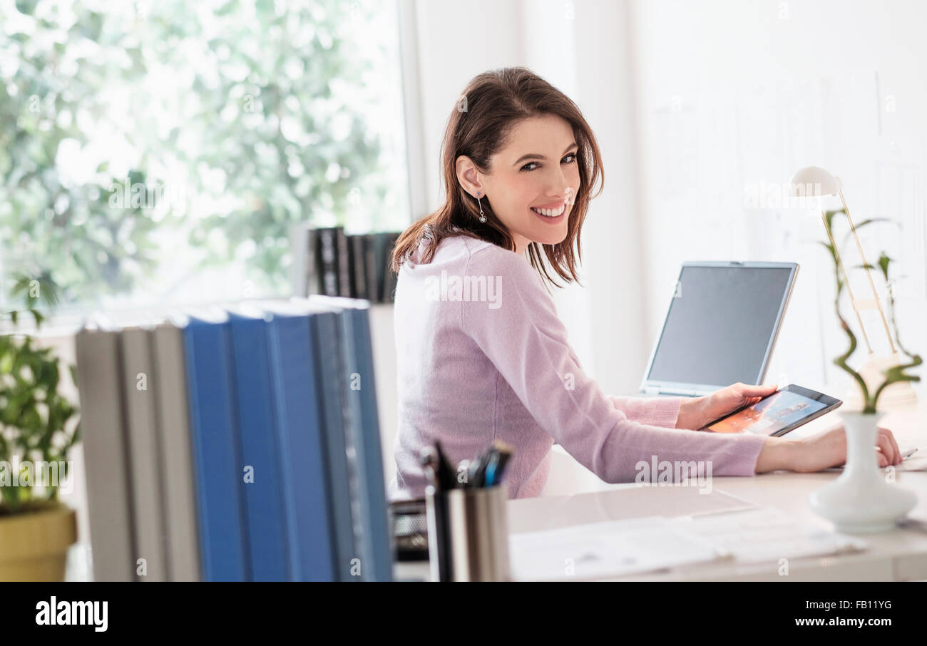 Young woman using digital tablet, looking at camera - Stock Image