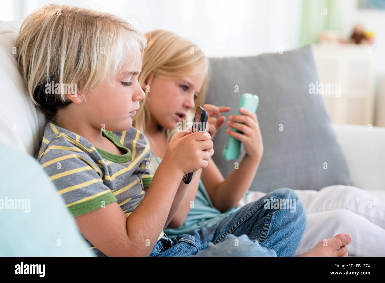 Boy (4-5) and girl (6-7) playing games on smart phones - Stock Image