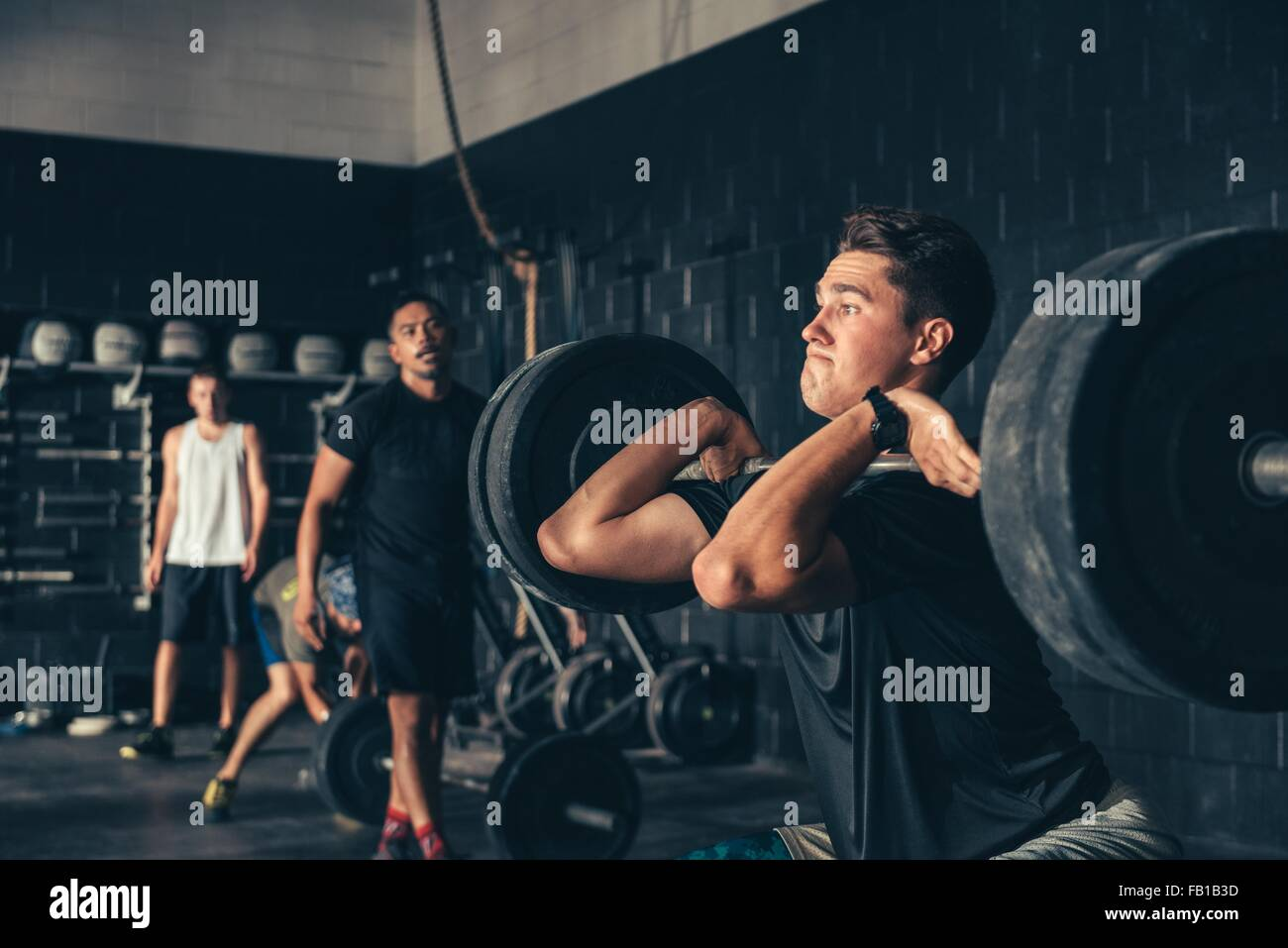 Man and trainer training with barbell in gym Stock Photo