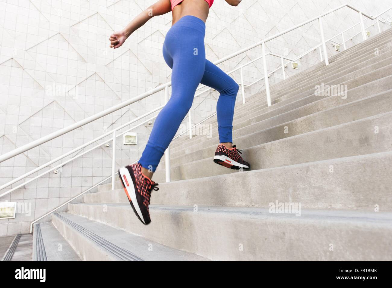 Low angle rear view of young woman, wearing sports clothing running up stairs - Stock Image