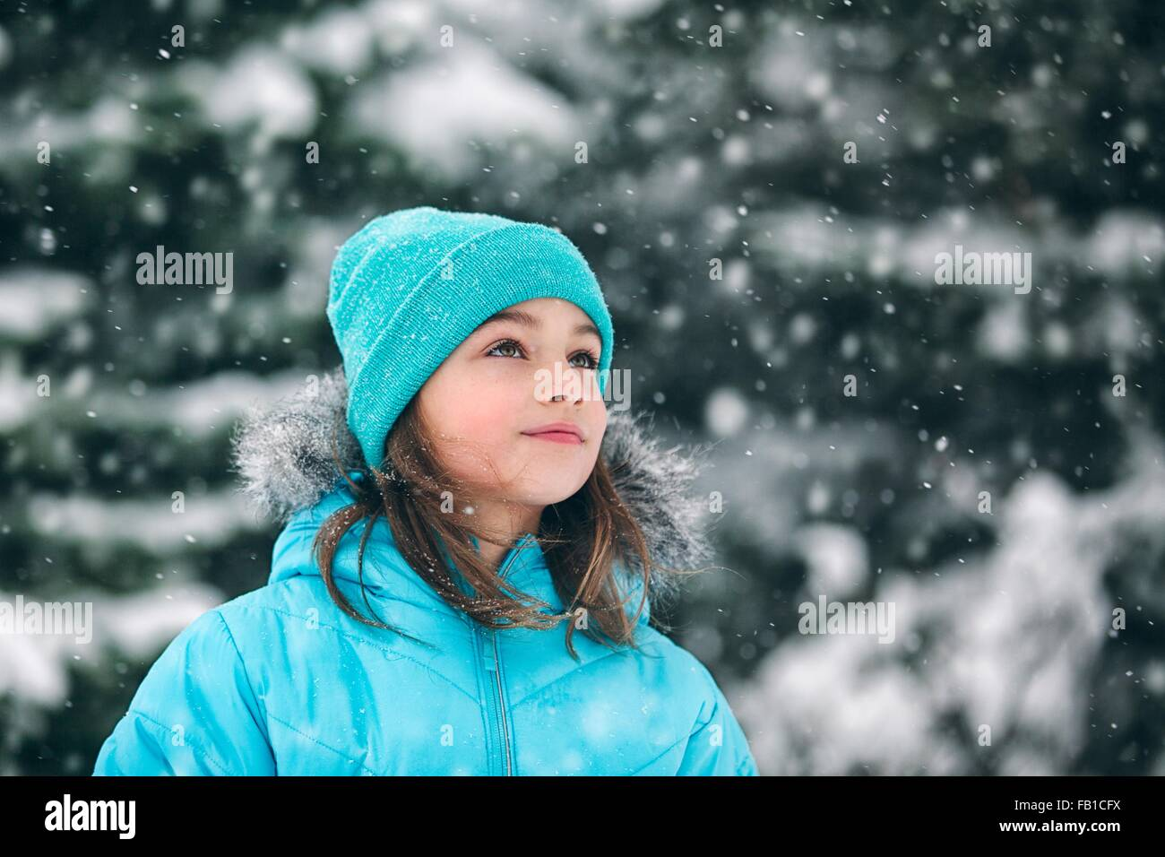 Girl wearing knit hat looking away, snowing - Stock Image