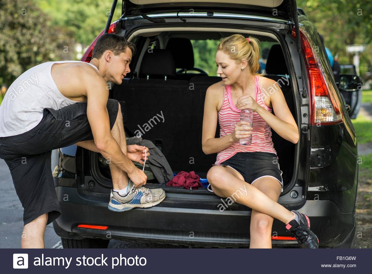 Young couple sitting in back of open car, preparing for hike - Stock Image