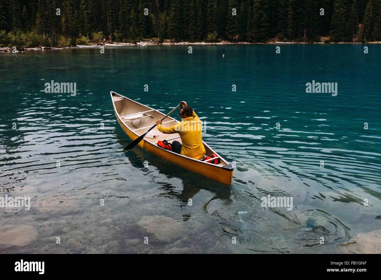 High angle rear view of mid adult man paddling canoe on Moraine lake, Banff National Park, Alberta Canada - Stock Image