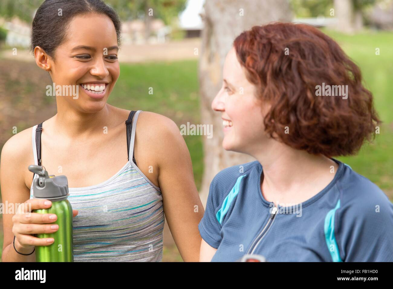 Head and shoulders of young women carrying water bottles face to face smiling - Stock Image