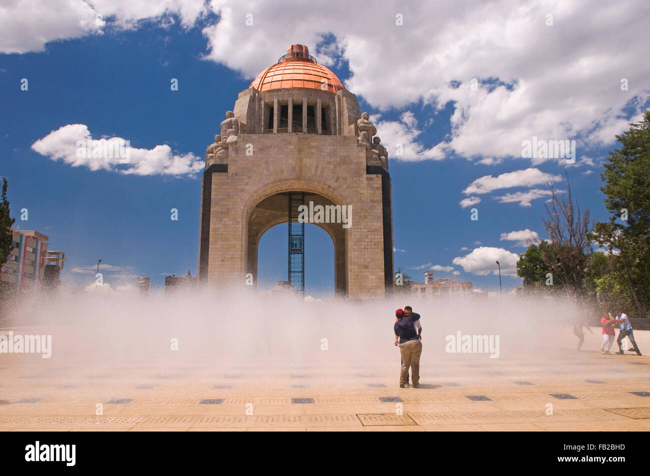 People relaxing in the fountain of the Arco de la Revolucion (Arch of the Revolution) in Mexico City, Mexico, South - Stock Image