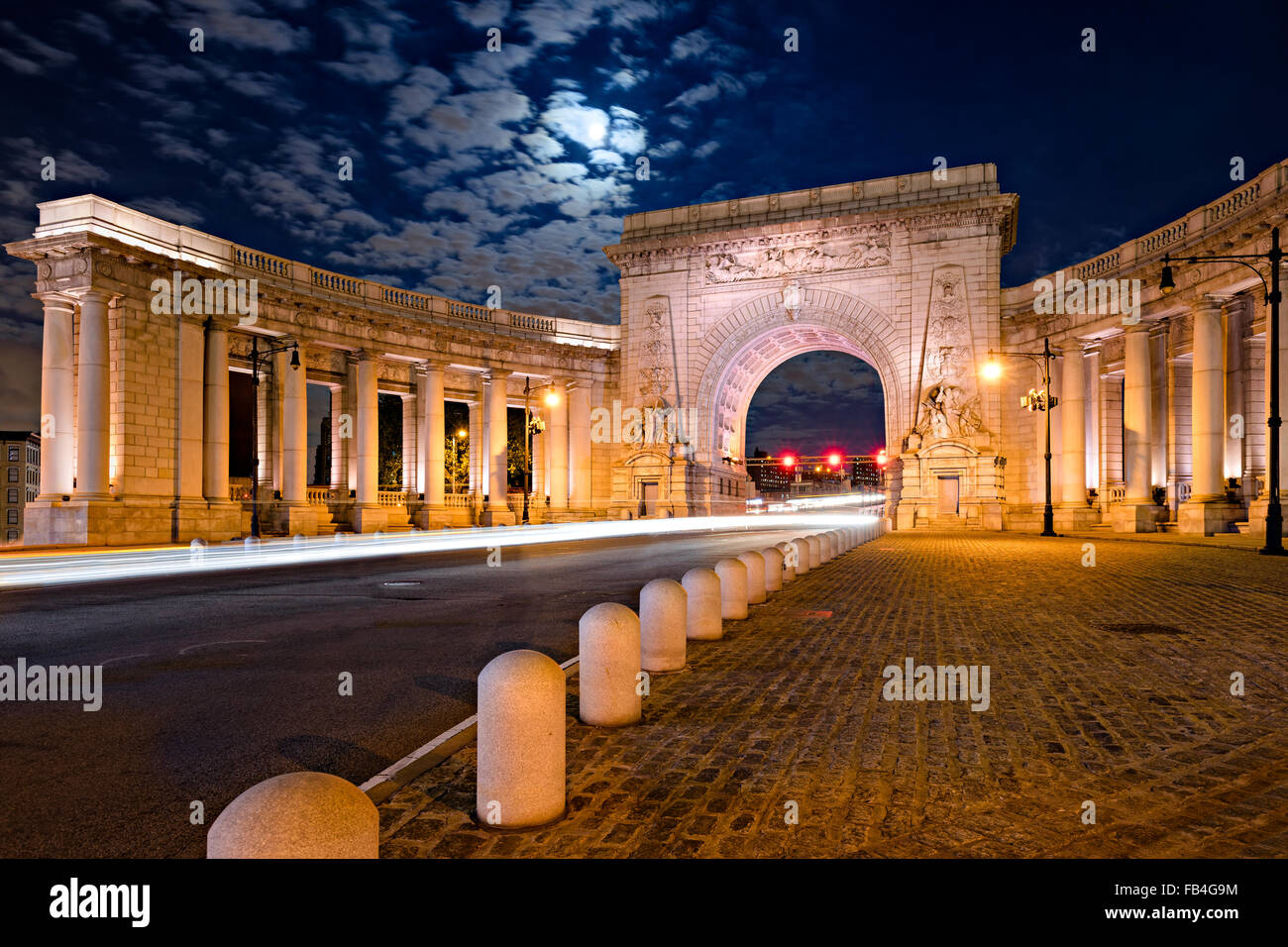 Illuminated Triumphal Arch and Colonnade of Manhattan Bridge Entrance in moonlight, Chinatown, Lower Manhattan, - Stock Image