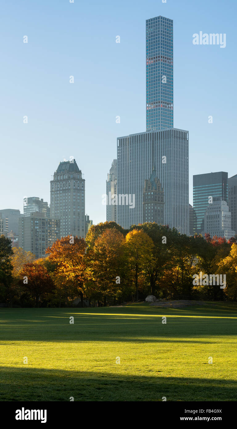Autumn sunrise in Sheep Meadow Central Park with view on Midtown Manhattan skyscrapers, including 432 Park Avenue. - Stock Image