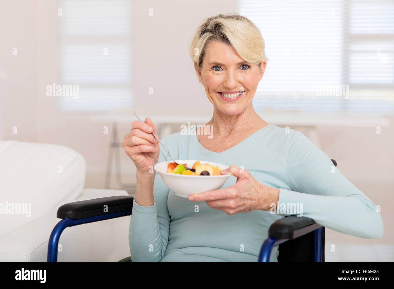 portrait of cute mature woman in wheelchair eating fruit salad stock