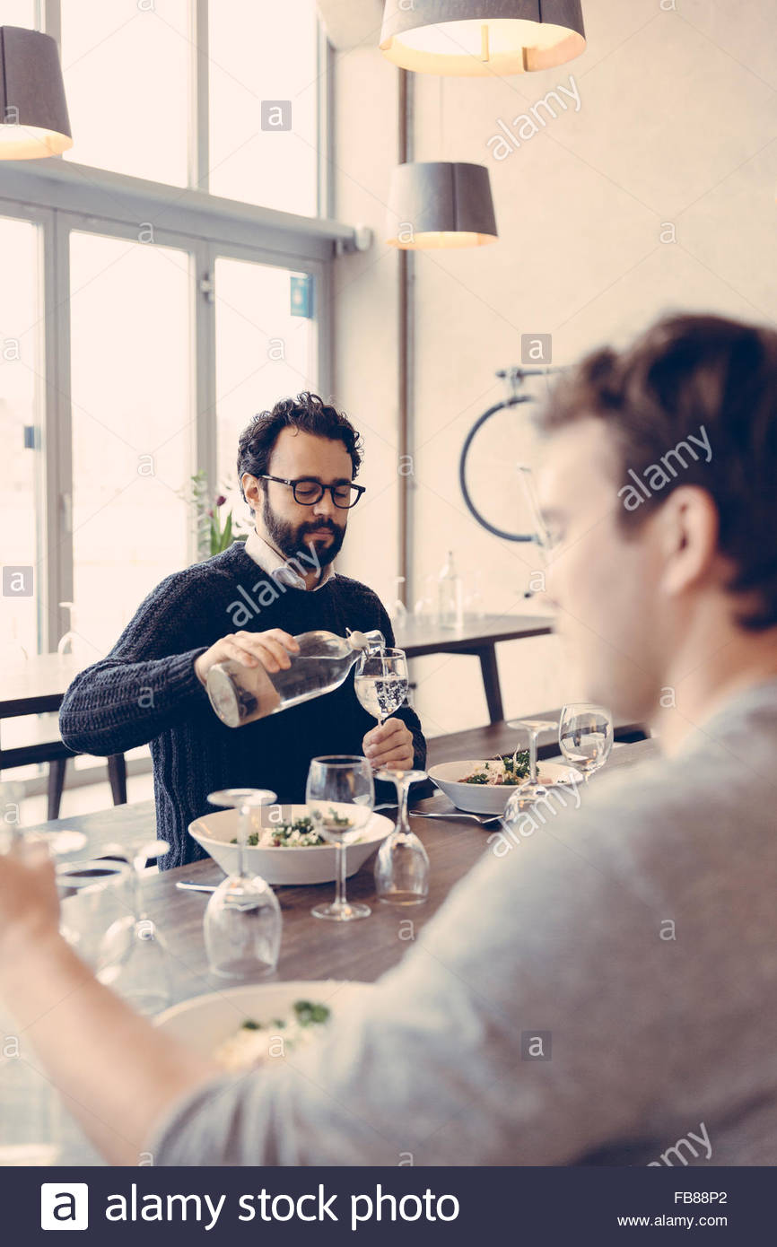 Sweden, Man pouring water into glass - Stock Image