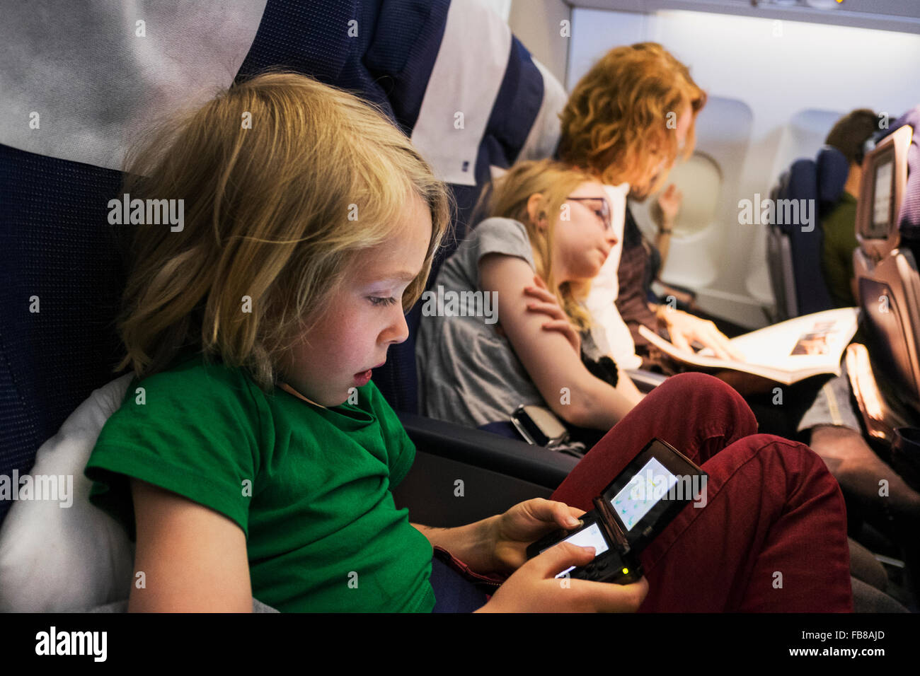 Sweden, Mother travelling by plane with children (6-7, 10-11) - Stock Image