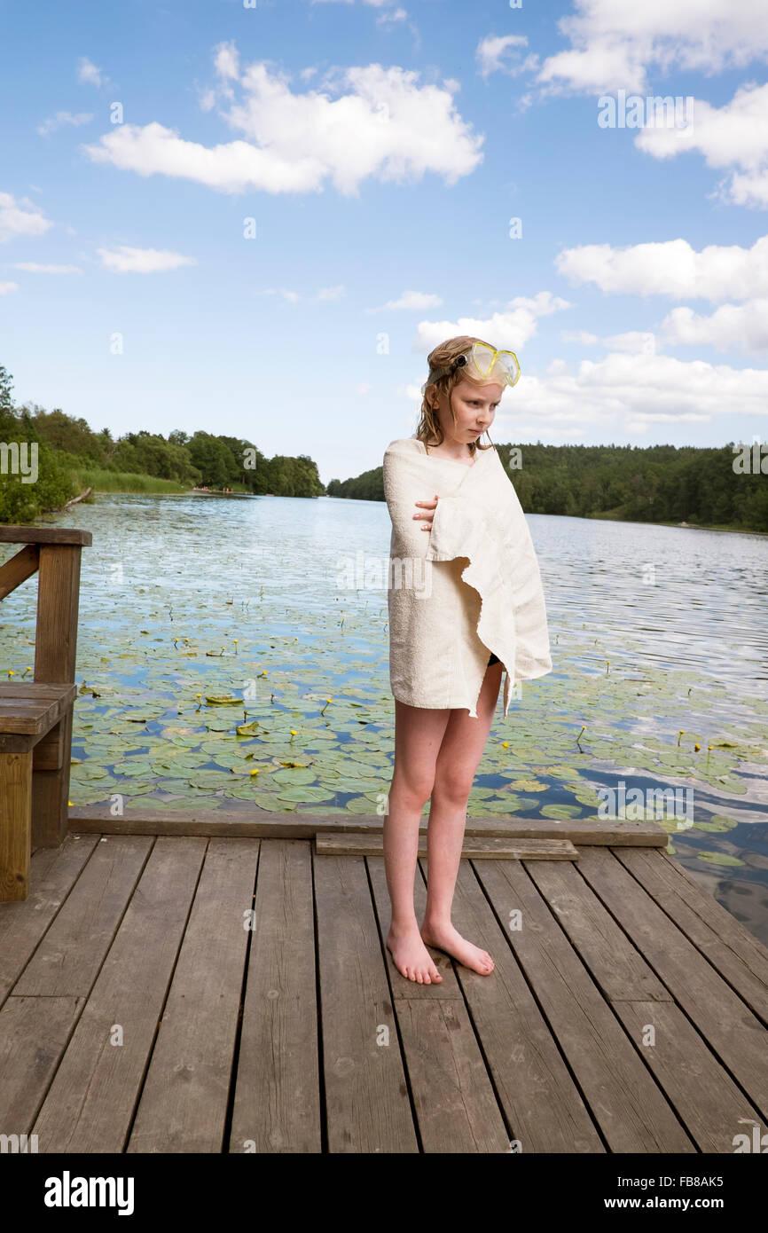 Sweden, Stockholm, Nacka, Sicklasjon, Lake Sickla, Girl (10-11) wrapped in towel standing on wooden jetty after - Stock Image