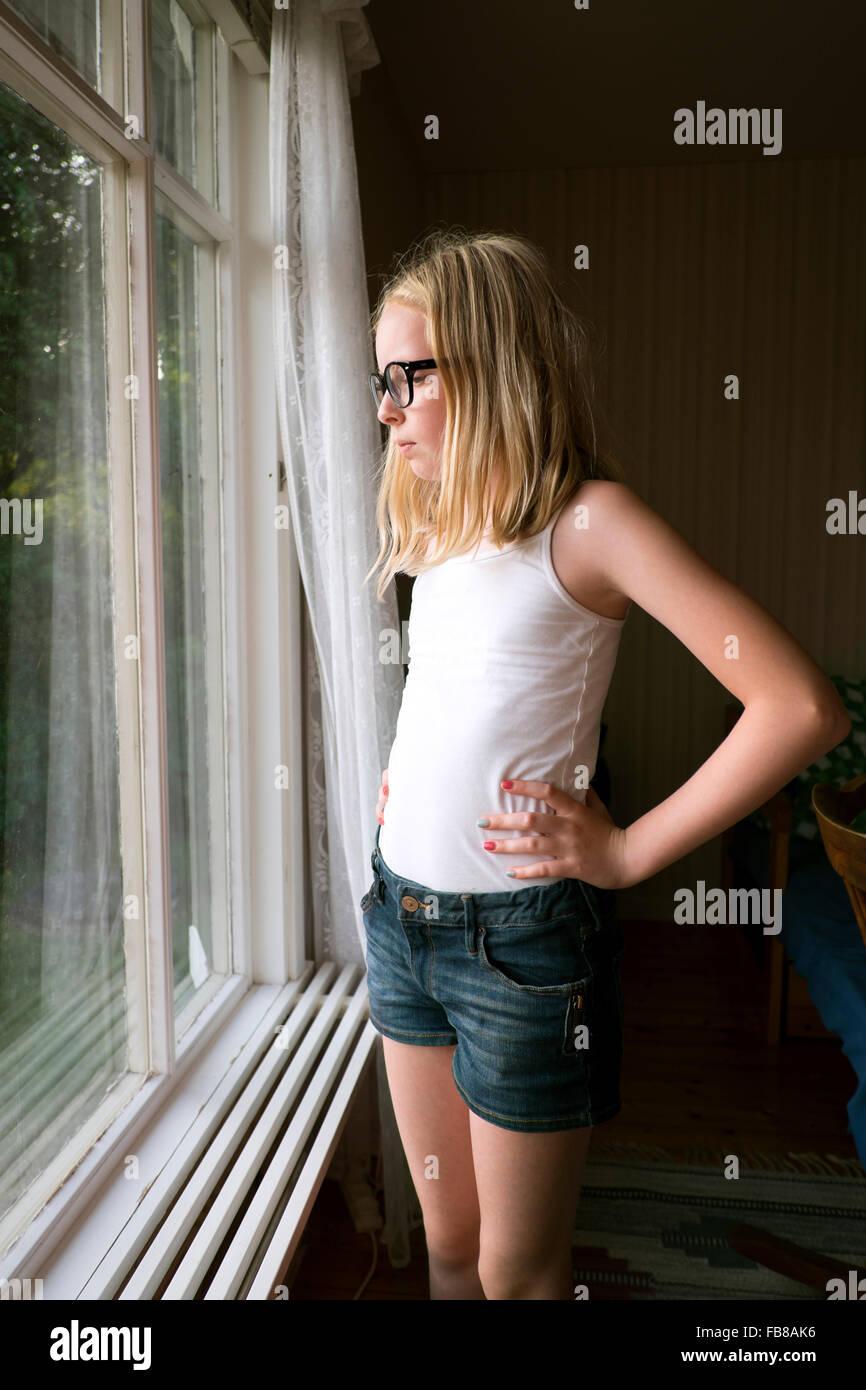 Sweden, Skane, Vejbystrand, Girl (10-11) looking though window - Stock Image
