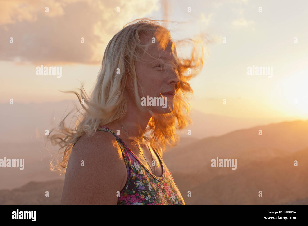 USA, California, Joshua Tree National Park, Female tourist relaxing in mountain landscape at sunset - Stock Image