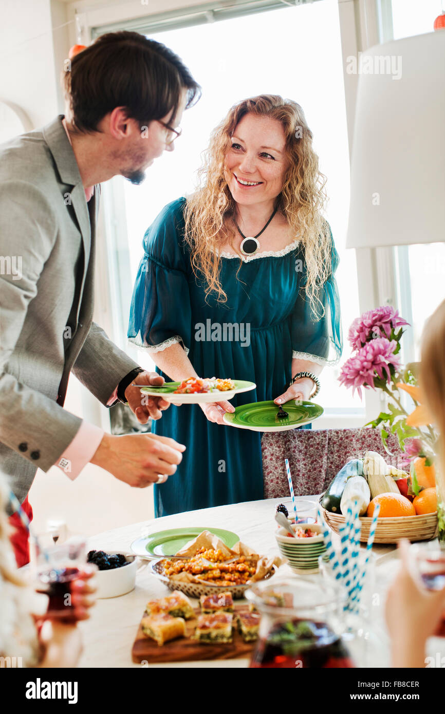 Sweden, Friends talking during party - Stock Image