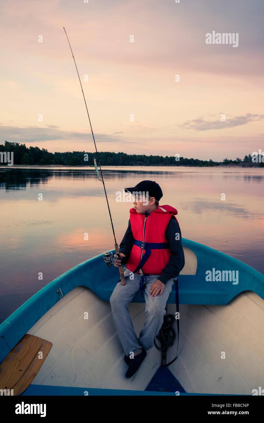Sweden, Smaland, Tjust archipelago, Vastervik, Hasselo, Boy (10-11) fly fishing in boat on lake - Stock Image