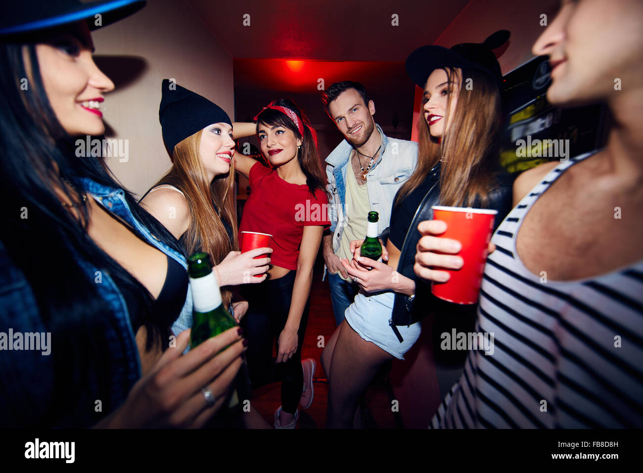Young stylish people with drinks gathering in bar - Stock Image